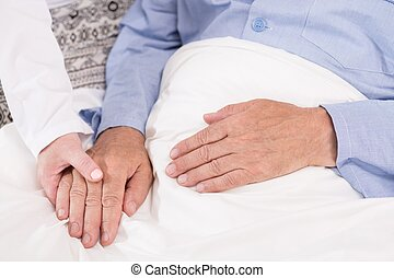 Nurse supporting old male patient - Close up of kind nurse...