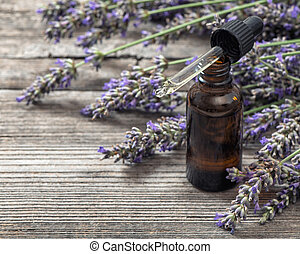 Herbal oil essence and dreied lavender flowers on wooden...