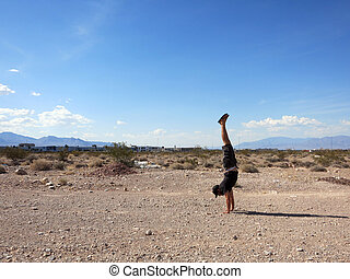 Man Handstanding in the Las Vegas Desert on a clear day