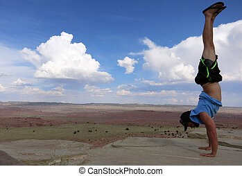 Man does Handstand on cliffs with field landscape