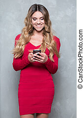 Attractive young woman in a red dress using smartphone -...