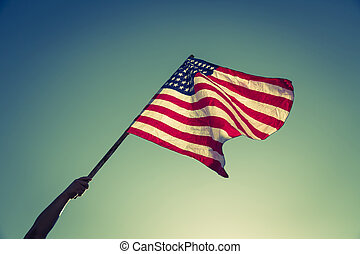 American flag with stars and stripes hold with hands against...