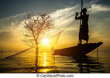 Silhouettes fisherman throwing fishing nets during sunset,...