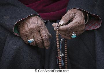 Old Tibetan woman holding buddhist rosary, Ladakh, India -...