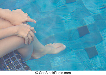 Female legs under the swimming pool water