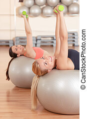 Women doing weights fitness on balls - Power lifting. Two...