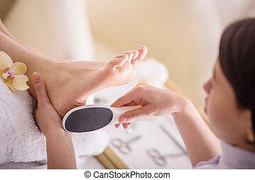 Spa treatment - Peeling feet pedicure procedure in a beauty...