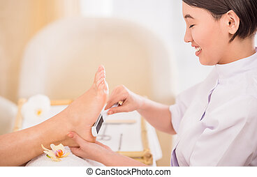 Spa treatment - Happy female pedicurist working on a client...