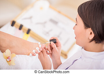 Spa treatment - Close-up of pedicurist applying nail polish...