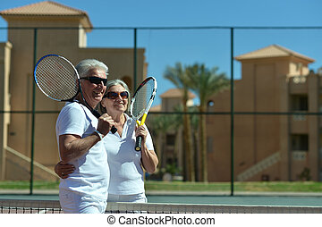 Senior couple on tennis court - Active senior couple on a...