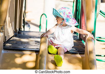 Toddler - Little girl playing outside on toddlers playground...