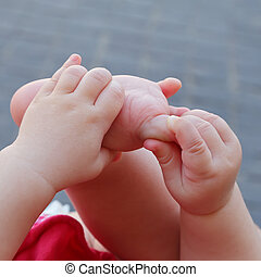 Newborn plays with hands and feet