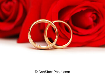 Two wedding rings and red roses isolated on white