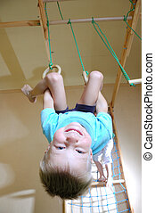 boy hanging on gymnastic rings - 5 year old boy hanging on...