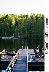 Dock or pier on lake in summer day. forest,  Finland