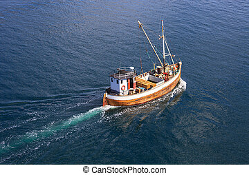 Fishing boat - Old wooden fishing boat trawler on sea.