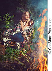 Pensive girl sitting near bonfire - Young pensive girl...