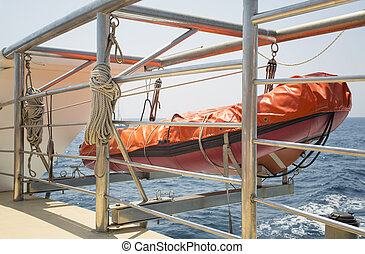 Lifeboat - orange lifeboat hanging on ship at sea