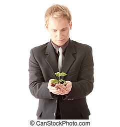 Man in suit holding smal plant in his hands - Businessman in...