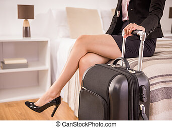 Business Trip - Business woman holding suitcase while...