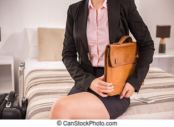 Business Trip - Business woman with briefcase sitting on bed...