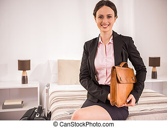 Business Trip - Business woman with her briefcase sitting on...