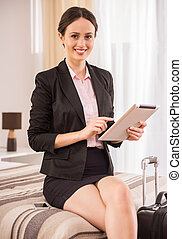 Business Trip - Business woman using her digital tablet and...