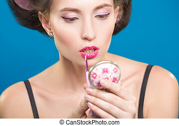 Sexy young pin-up girl doing make-up
