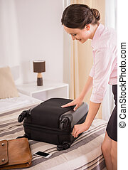 Business Trip - Young business woman packing her suitcase on...