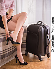 Business Trip - Business woman taking down her shoes while...