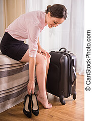 Business Trip - Business woman putting down her shoes while...