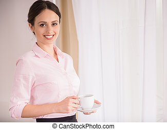 Business Trip - Businesswoman standing with cup of coffee...