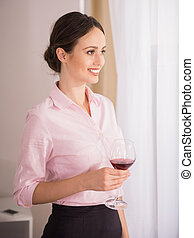 Business Trip - Business woman standing with glass of wine...