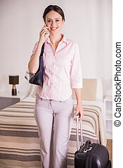 Business Trip - Attractive business woman talking by phone,...