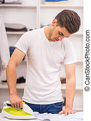 Man in dressing room - Young man concentrated on ironing in...