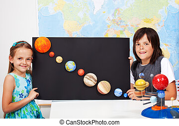 Kids in science class study the solar system