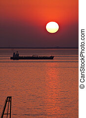 Silhouette of tank ship moored at anchor against red sunset...