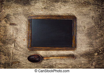 Wooden spoon and Blackboard on a rustic dark background