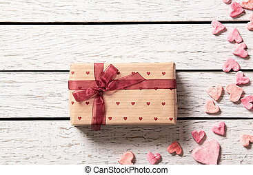 Vintage gift box with heap of small hearts on white wooden...
