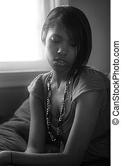 Alone with her thoughts - A beautiful female sitting by a...