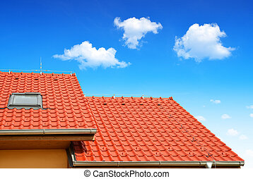 House with tiled roof on blue sky.