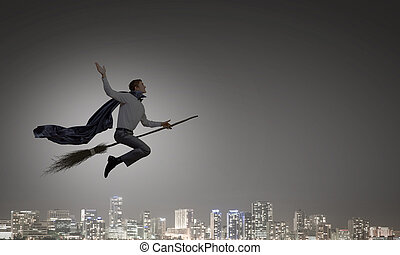Man ride broom - Young businessman flying on broom high in...