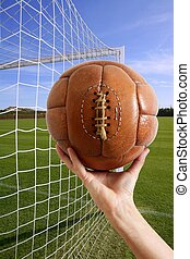 Football in hand net soccer goal
