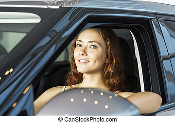 My new car - Young pretty woman in car salon sitting in car