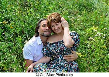 loving couple sitting on the grass in summer - A loving...