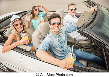 Friends in cabriolet - Group of happy friends traveling on...