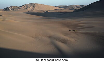 Dune Buggy and Dunes - Dune buggy crossing a desolate barren...