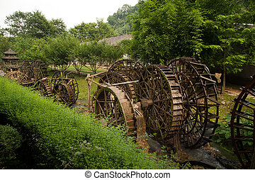 Waterwheel front of entrance to Huanglong cave in China -...