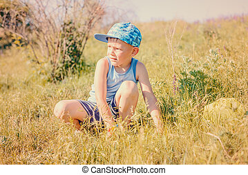 Small boy catching insects in summer crouching down in the...