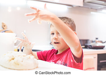 Little boy playing with dough in the kitchen